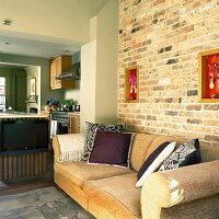 Suite of rooms in a country home: living room with sofa against a brick wall, kitchen with island and dining nook