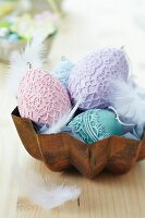 Various Easter eggs decorated with lace doilies and feathers in metal cake mould