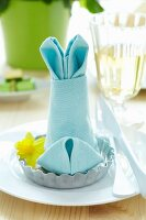 Napkin folded into shape of bunny in tartlet tin