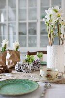 Festive table decoration with hyacinths and hellebores in original containers combined with crystal glasses and floral cups