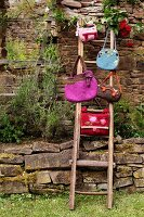 Various hand-made felt bags hanging from ladder against stone wall