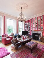 Grand interior in hot pink with pink animal-skin rug and large gallery of pictures on chimney breast above open fireplace; silver beanbag under coffee table