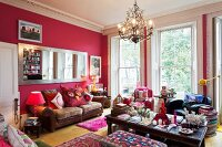 Hot pink walls in grand room with large, long, wall-mounted mirror, leather couch and floor-to-ceiling windows