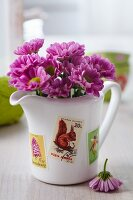 Flowers in jug decorated with postage stamps