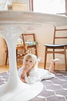 Little girl in nightie lying under table eating a biscuit