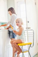 Little girl with ice lolly sitting on chair in kitchen