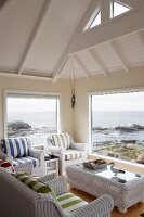 White wicker lounge set with striped upholstery below wood-panelled roof space; view of stony coast and sea through panoramic window