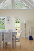 Panoramic window with view of mountain landscape beyond maritime dining table with white wicker chairs