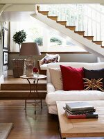 Sofa with scatter cushions and coffee table in front of platform with steps below staircase in elegant country house