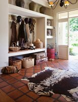 Rustic entrance area with animal-skin rug on terracotta tiled floor; clothing in open-fronted, vintage coat rack