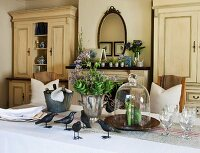 Festively set table in rustic setting with metal bird figurines and flowers and bottles in various containers; open fireplace in background