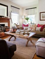 Various upholstered seating around wooden coffee table in country-style living room; windows with striped Roman blinds