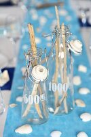 Maritime table decoration: twigs in glass bottles
