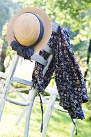 Romantic dress and straw hat on garden chair