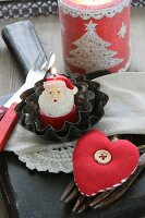Christmas table decoration with Father Christmas candle in small cake tins, cutlery and fabric heart