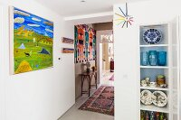 Decorative crockery in fitted cupboard and view along hallway with colourful ethnic decor and Aboriginal paintings