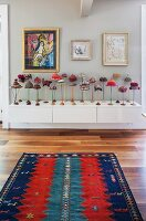 Artistic collection of Oriental and African hats presented on stands of various woods; colourful kilim rug from Azerbaijan in foreground