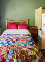 Double bed with colourful patchwork bedspread and small pillows in guest room painted olive green