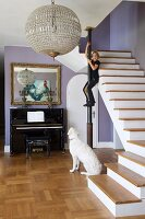 Antique, spherical, crystal pendant lamp in renovated foyer; girl climbing on metal pillar next to staircase