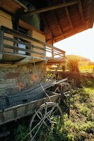 Old hay cart in front of farmhouse with balcony in rural setting