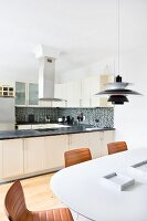 Leather chairs at white table below Poulsen pendant lamp in front of open-plan fitted kitchen with U-shaped counter