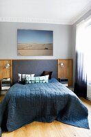 Double bed with dark blue spread and fabric and wooden headboard panel on wall below photo of desert in traditional bedroom