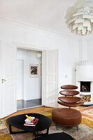 Black metal coffee table in front of classic office chair with brown leather cover and matching footstool; open double doors in background next to white corner fireplace