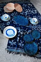 Blue and white patterned crockery and wooden plates on colour-coordinated cloth