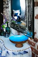 Blue-glazed bowl and smoked glass vases of lupins on console table below antique mirror on brick wall