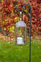 Candle lantern hanging on metal crook in garden