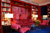 Red bookcase in modern living room with large painting and blue floor