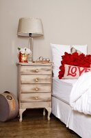 Shabby-chic, renovated bedside cabinet next to white bed with bright red cushions