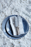 Hand-crocheted knife covers on knives and blue plate on white artificial snow