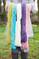 Woman holding up yarns of different colours