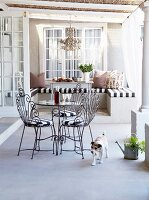 Pretty wire chairs and table with glass top on romantic country-house terrace