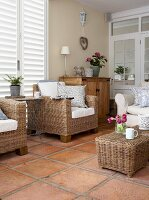 Wicker armchairs and stool on terracotta tiled floor in romantic, country-house interior