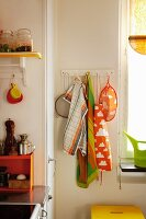 Colourful tea towels on hooks in corner of kitchen next to window