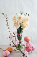 Easter arrangement of dyed eggs, narcissus & sprig of cherry blossom
