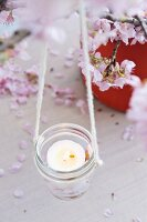 Candle lantern hanging from blossoming cherry branch
