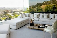 White sofa combination in corner of living room with panoramic view over city and landscape reflected in glass wall