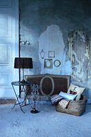 Table lamp with black lampshade on side table next to candelabra and basket on floor in front of wall with crumbling plaster