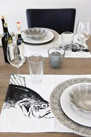 Table settings with grey plates on black and white placemats with fish motifs