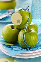 Green apples with satin ribbon and tag on stacked plates