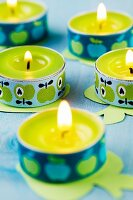 Tealights wrapped in ribbons with apple motifs