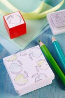 Small gift boxes stamped with apple motifs