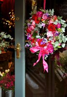 Wreath in various shades of red and pink hanging on glass door with brass fittings