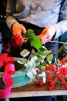 Hands of woman cutting rose for flower wreath with oasis foam base
