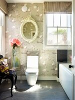 Eclectic bathroom with flamingo motif on wallpaper & nostalgic oval mirror on wall above modern toilet