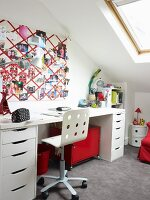 Fabric pin board above teenager's desk in bright attic bedroom