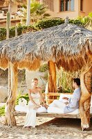Honeymoon - newly married couple on sun lounger under palm leaf roof on beach